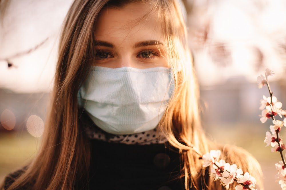 brunette woman outside wearing a disposable face mask