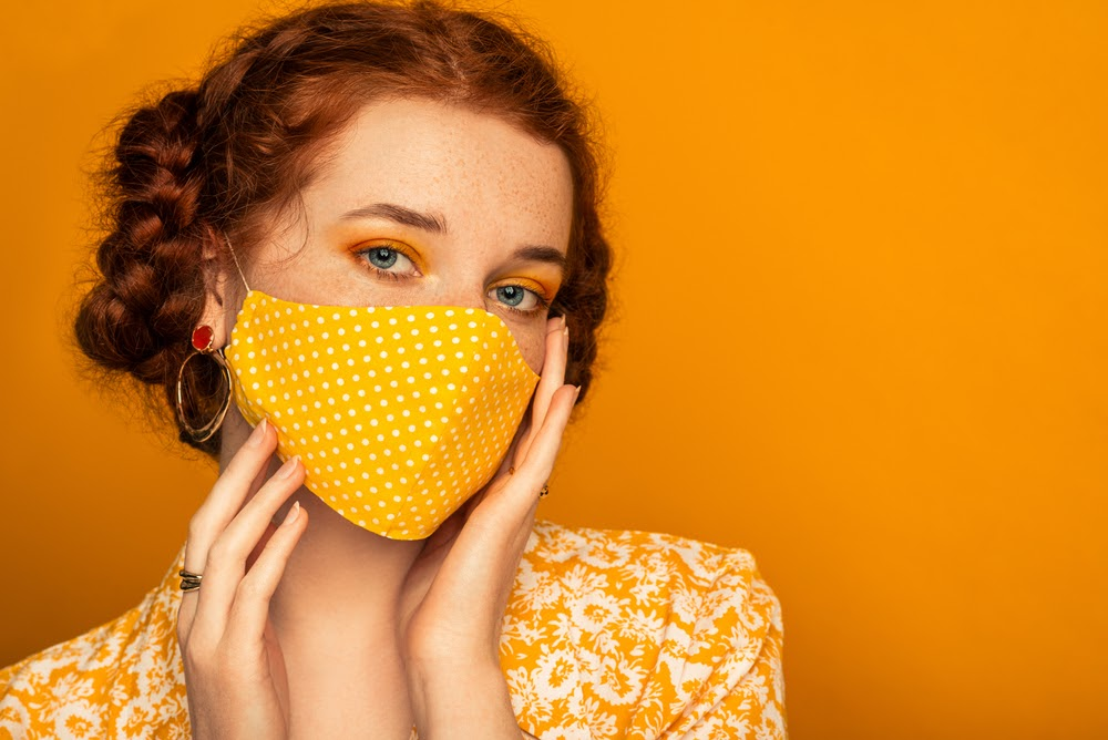 red haired woman standing in front of an orange wall wearing a yellow mask