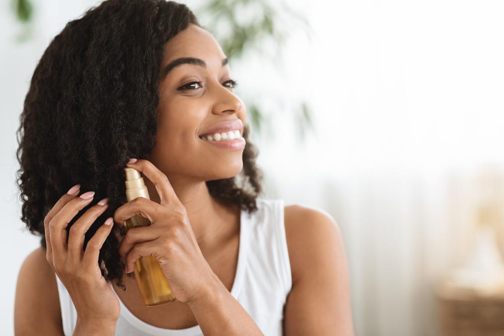 woman applying hair oil to her hair